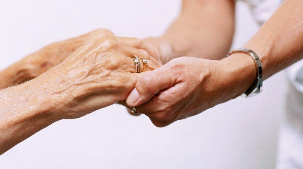 Deux personnes qui se tiennent les mains, signe d'entraide, de bienveillance.